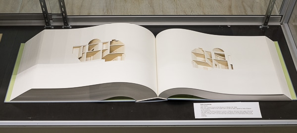 The artist's house is laser cut slice by slice out of the pages of this giant book.
